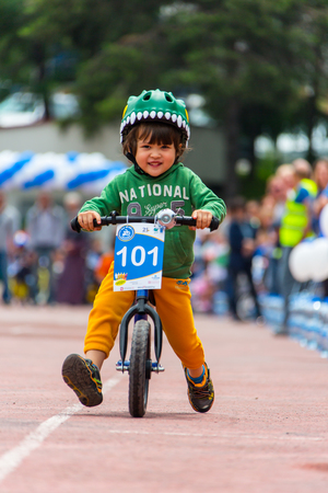 KAZAKHSTAN, ALMATY - JUNE 11, 2017: Childrens cycling competitions Tour de kids. Children aged 2 to 7 years compete in the stadium and receive prizes. Little boy rides a tricycle on the road Editorial