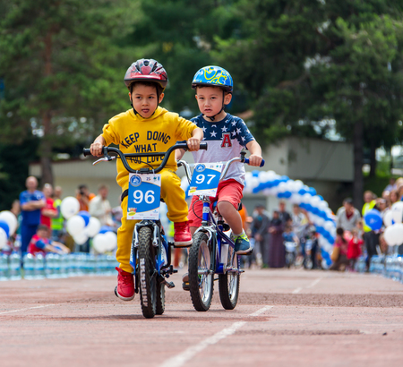 compete: KAZAKHSTAN, ALMATY - JUNE 11, 2017: Childrens cycling competitions Tour de kids. Children aged 2 to 7 years compete in the stadium and receive prizes. Portrait of three little cyclists riding their bikes