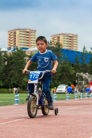 compete: KAZAKHSTAN, ALMATY - JUNE 11, 2017: Childrens cycling competitions Tour de kids. Children aged 2 to 7 years compete in the stadium and receive prizes. Portrait of a cute boy on bicycle