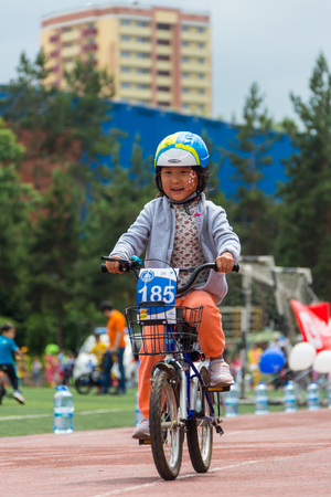 compete: KAZAKHSTAN, ALMATY - JUNE 11, 2017: Childrens cycling competitions Tour de kids. Children aged 2 to 7 years compete in the stadium and receive prizes. The girl on a bicycle rides on a sports stadium and competes to win.