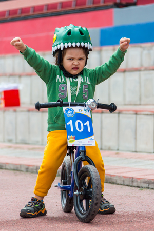 compete: KAZAKHSTAN, ALMATY - JUNE 11, 2017: Childrens cycling competitions Tour de kids. Children aged 2 to 7 years compete in the stadium and receive prizes. Little boy rides a tricycle on the road Editorial