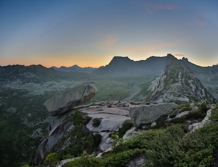 Hanging stone lies on sloping surface of mountain above precipice. A huge boulder of granite and syenite is supported by a small area on mountain. Ergaki Park. Russia