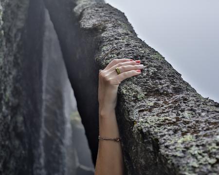 Bergsteigerhände der jungen Frau, die am Küstenbergklippenfelsen klettern. Standard-Bild