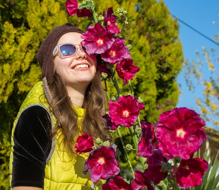 Adorable girl sniffing purple flowers. Women and flowers, summer, nature and fun. Summer holidays.