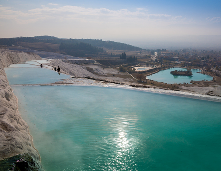 The enchanting pools of Pamukkale in Turkey. Pamukkale contains hot springs and travertines, terraces of carbonate minerals left by the flowing water. 스톡 콘텐츠