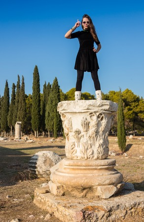 Beautiful Greek young girl holding an ancient vessel in ancient theatre of Thassos island, Greece