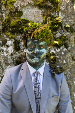 Office worker in a business suit, outdoors with a make-up on his face and green moss on his head. Man merges with nature. Banque d'images