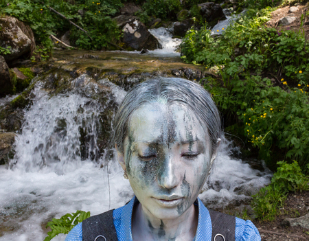Girl Office worker, outdoors with a makeup on her face imitating a mountain stream. The girl merges with the river and the environment.