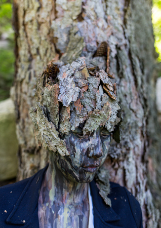 Girl Office worker in a business suit, outdoors with a makeup on her face imitating the bark of a tree. The girl merges with the tree trunk, sits and rests her back on him.