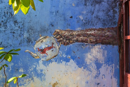 Image on an old wall - hand pours tea from a Chinese teapot