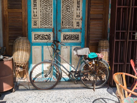 Old bicycle leaning against grungy barn in Thailand Stock Photo