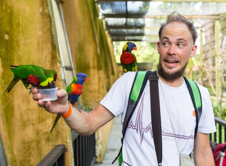 Man with parrots sitting on the shoulder and head