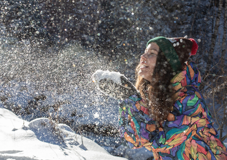Beauty Winter Girl Blowing Snow in frosty winter Park. Outdoors. Flying Snowflakes. Sunny day. Backlit. Joyful Beauty young woman Having Fun in Winter Park. Stock fotó