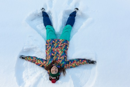High angle view of happy girl lying on snow and moving her arms and legs up and down creating a snow angel figure. Smiling woman lying on snow in winter holiday with copy space Imagens - 116178109