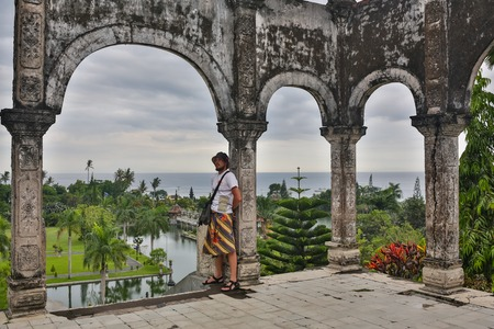 Young man tourist in old water palace on Bali island. Stock Photo