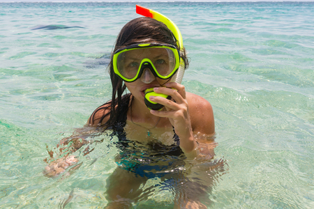 Beach vacation fun woman wearing a snorkel scuba mask making a goofy face while swimming in ocean water. Closeup portrait of Asian girl on her travel holidays. Summer or winter destination.