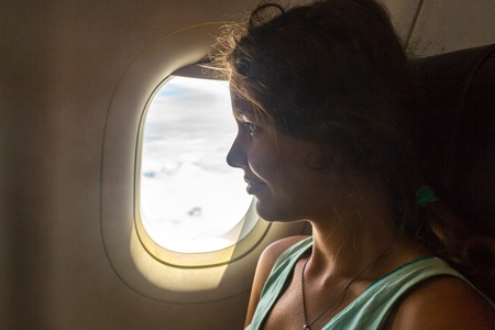 Young woman on passenger seat near window in airplane