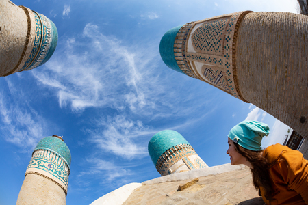 The girl on the roof of the mosque Chekminar - four minarets, in the city of Bukhara, Uzbekistan Stockfoto