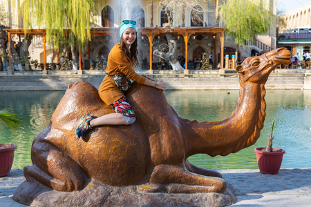 happy girl taking crazy selfie with the statue of camel Bukhara, Uzbekistan Stockfoto