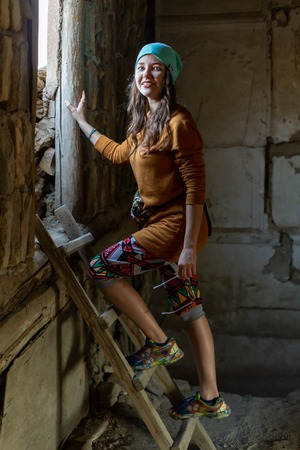 A girl walks up the stairs in an old house, facing the light