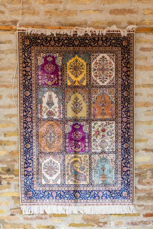 The wide range of the hand made carpets in traditional style in the small stall at Toqi Sarrafon bazaar, Bukhara, Uzbekistan.