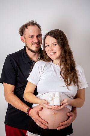 Immagine ritagliata di una bella donna incinta e del suo bel marito che abbracciano la pancia