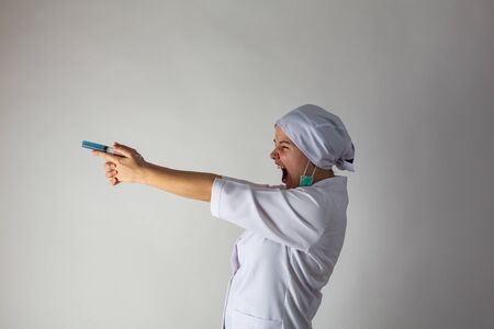 The girl in a medical coat holds a large syringe with blue liquid like a gun Banque d'images - 144164291