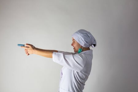 The girl in a medical coat holds a large syringe with blue liquid like a gun Banque d'images - 144164296