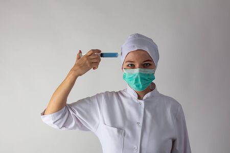 The girl in a medical coat holds a large syringe with blue liquid like a gun.