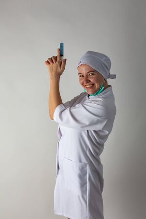 The girl in a medical coat holds a large syringe with blue liquid like a gun Banque d'images - 144164297