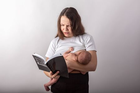 Beautiful young mother breastfeeding a baby while reading a black book