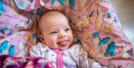 pretty smiling baby girl and toy rabbit lying in light background Standard-Bild