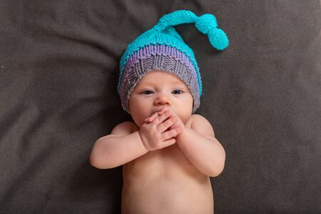 Beautiful baby girl in the studio on a dark gray background in bare pants and a winter hat.