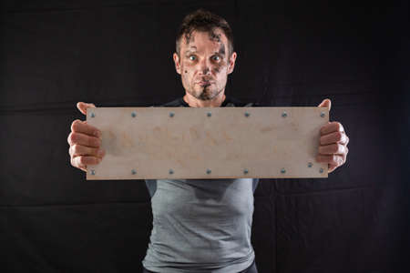 A sporty man holding an empty wooden sign with screws on a black background. Concept for inserting any word