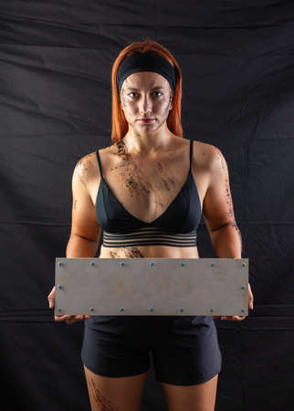 sports girl in mud holds a blank sign in the studio on a black background