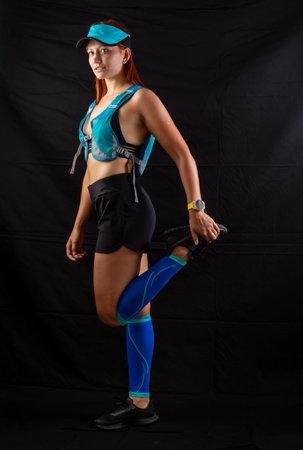girl in blue jogging uniform runs in the studio on a black background