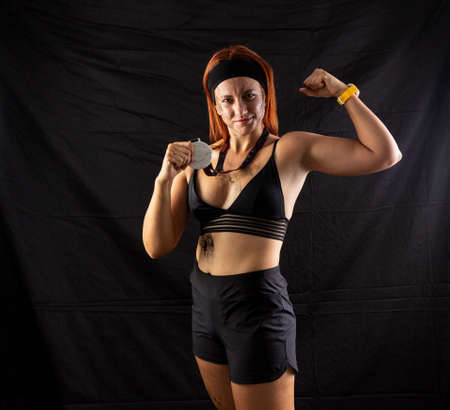 Beautiful redhead girl in sportswear with a silver medal in the studio on a black background