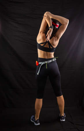 Beautiful girl in a jogging red uniform warming up before training in the studio on a black background