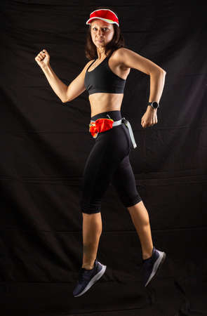 girl in red jogging uniform runs in the studio on a black background Stock Photo