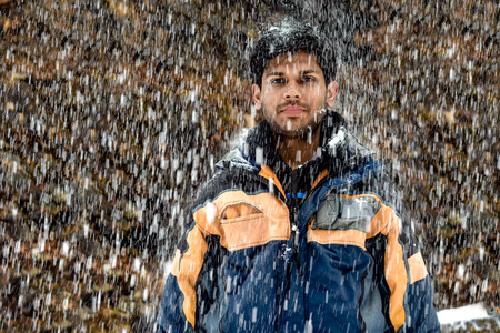 Young, Fair and Handsome Indian boy in his early 20 in skiing costume, wearing snowsuit, standing still and posing in neutral mood during heavy snowfall in winters during the onset of Christmas