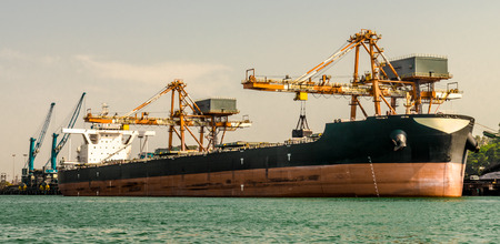 A Bulk Cargo shipvessel berthed at the Harbor, being offloaded by grabs of cranes. Visible are vessels draft marking which depicts that it is nearly emptied and contains no ballast. Import & Export