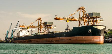 Ein Massengutfrachter/Schiff liegt im Hafen und wird von Greifern von Kränen entladen. Sichtbar ist die Tiefgangsmarkierung des Schiffes, die anzeigt, dass es fast geleert ist und keinen Ballast enthält. Import Export