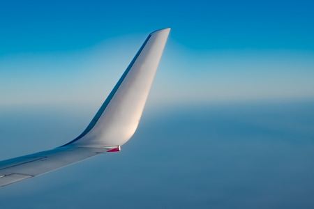 Beautiful photo of Winglet of an Airplane, taken from the window side, during air travel at very high Altitude with crystal clear Blue atmosphere outside the window. Reklamní fotografie
