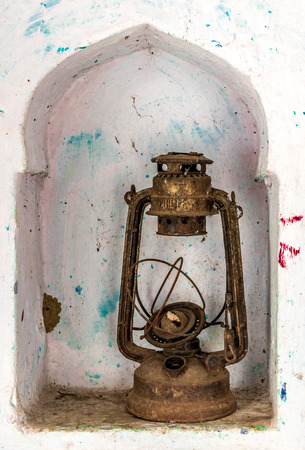 Beautiful photo of an obsolete and antique kerosene oil lantern kept in a wall shelf, once widely used as a source of light in rural India and Asia, now defunct owing to development and less powercuts Stockfoto