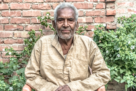 Portrait of Old aged Indian male in his early 80s, with white beard, wearing pale clothes, posing for camera, sitting relaxed on chair in backyard garden. He is leading satisfied post-retirement life.