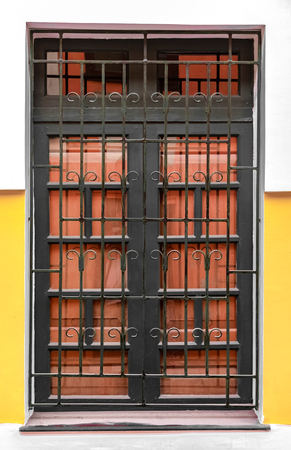 Very Beautiful Corinthian Style Big Window, having Iron Bars with patterns and Wooden Gate attached to it. A Typical Colonian Era Roman Architecture. - Image 写真素材