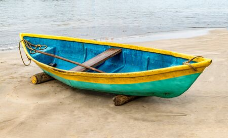 Beautiful photo of beached Fishing Canoe, the canoe is painted colorful in traditional asian manner.