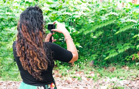 Trendy brunette botanist in her 20s, with curly hairs, is monitoring natural growth of plants during outdoor field work, and is exploring the natural beauty while clicking picture from action camera.
