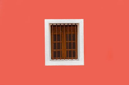 Beautiful background photo of Exterior wall, painted fresh with solid color of peach. The wall is clean, plain and a Vintage Wooden Window with white outline is adding further glam. -Image Imagens