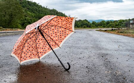Beautiful Umbrella having Polka dots on it, is lying on a empty road in rainy season of Tropical South India. The climate is very pleasant and lush green mountains in the background with cloudy sky.